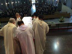 8人の若者司祭たちが運ぶ