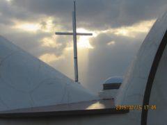 聖堂の屋根の十字架と沈み行く太陽