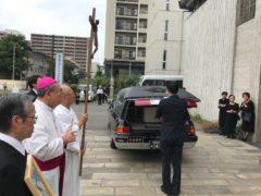 若手司祭団の手で霊柩車の中へ